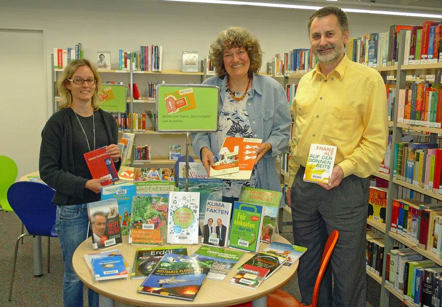 Dietmar Helmer, Vorsitzender des Vereins Bürgerstrom, Ute Kronmüller, Energiemanagement der Stadt Remseck, und Büchereileiterin Kathrin Pohl (links) zeigen den Büchertisch in der Bücherei Hochberg.